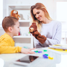 woman giving stuff toy to a boy